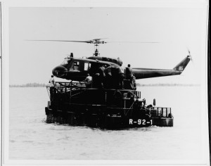 A U.S. Army UH-1D helicopter lands on the helicopter pad of a modified U.S. Navy Armored Troop Carrier (ATCH R-92-2) operating as part of the Riverine Mobile Force, 8 July 1967. Photography by Photographer's Mate Second Class Edward Shinton. USN 1132291 (NNHC photograph).